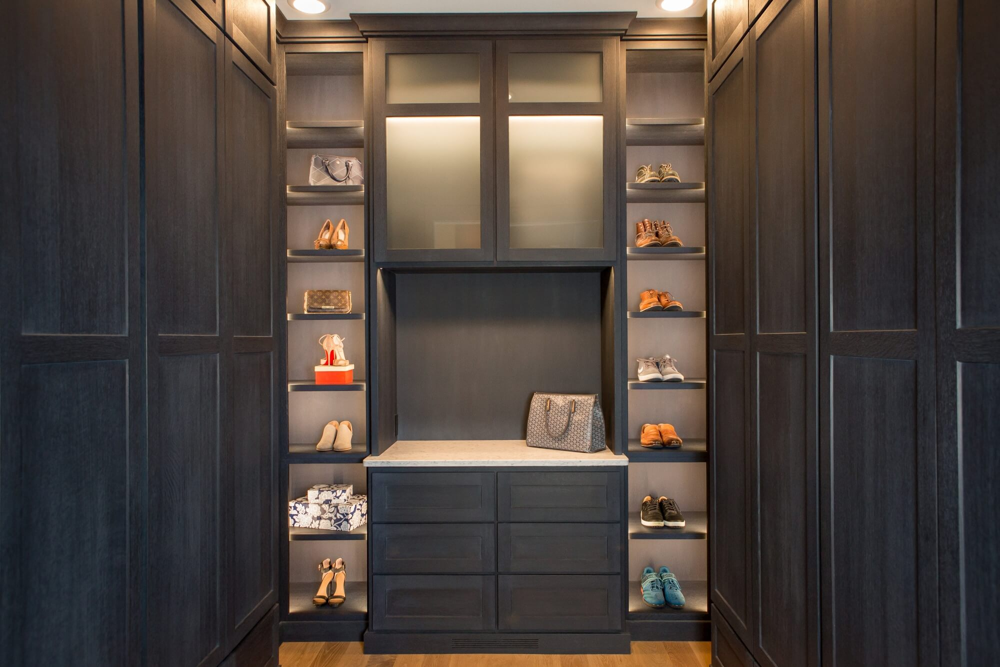 Luxury closet with shoe shelving and dark cabinetry.