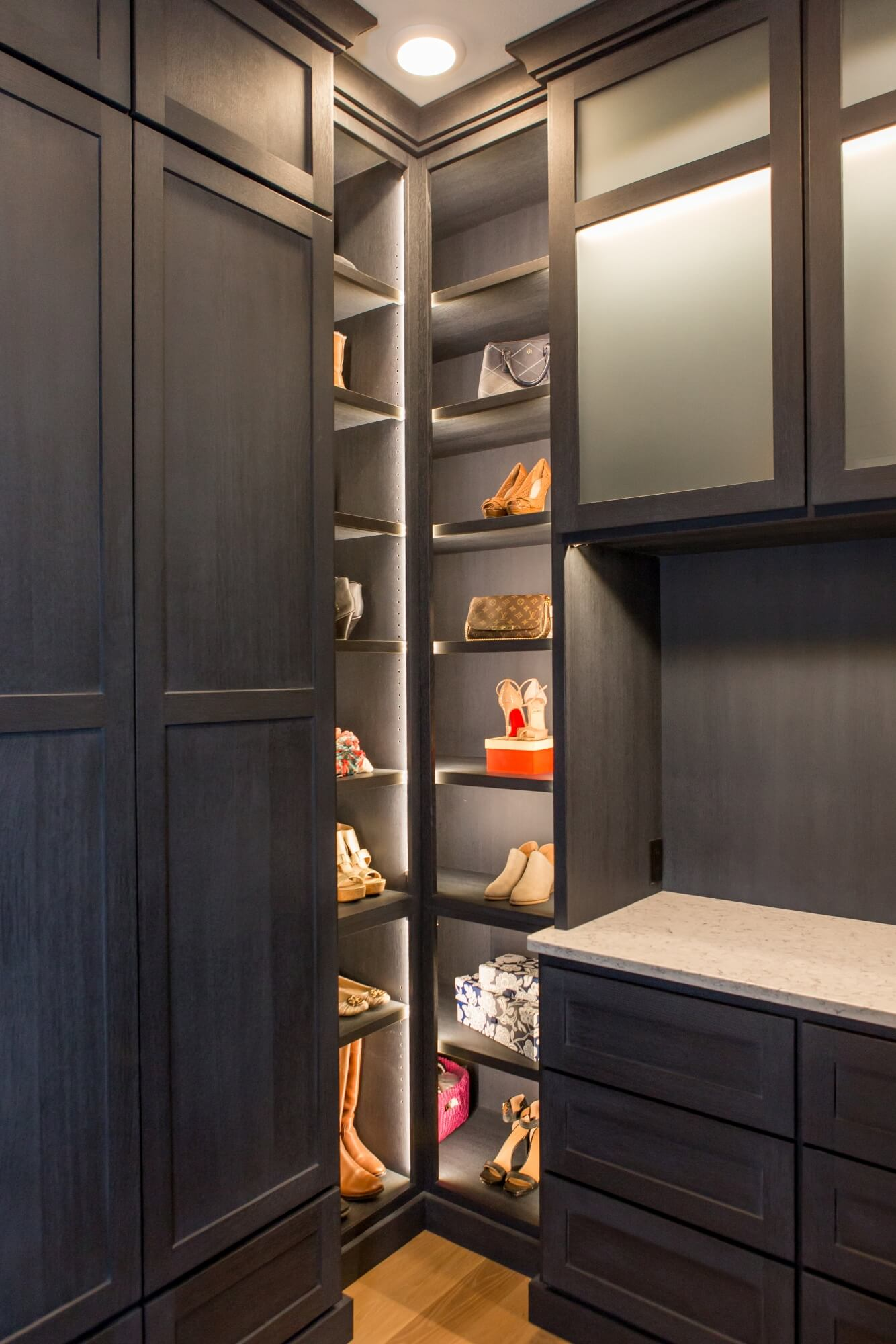 Corner of a large closet with built in shoe shelves.