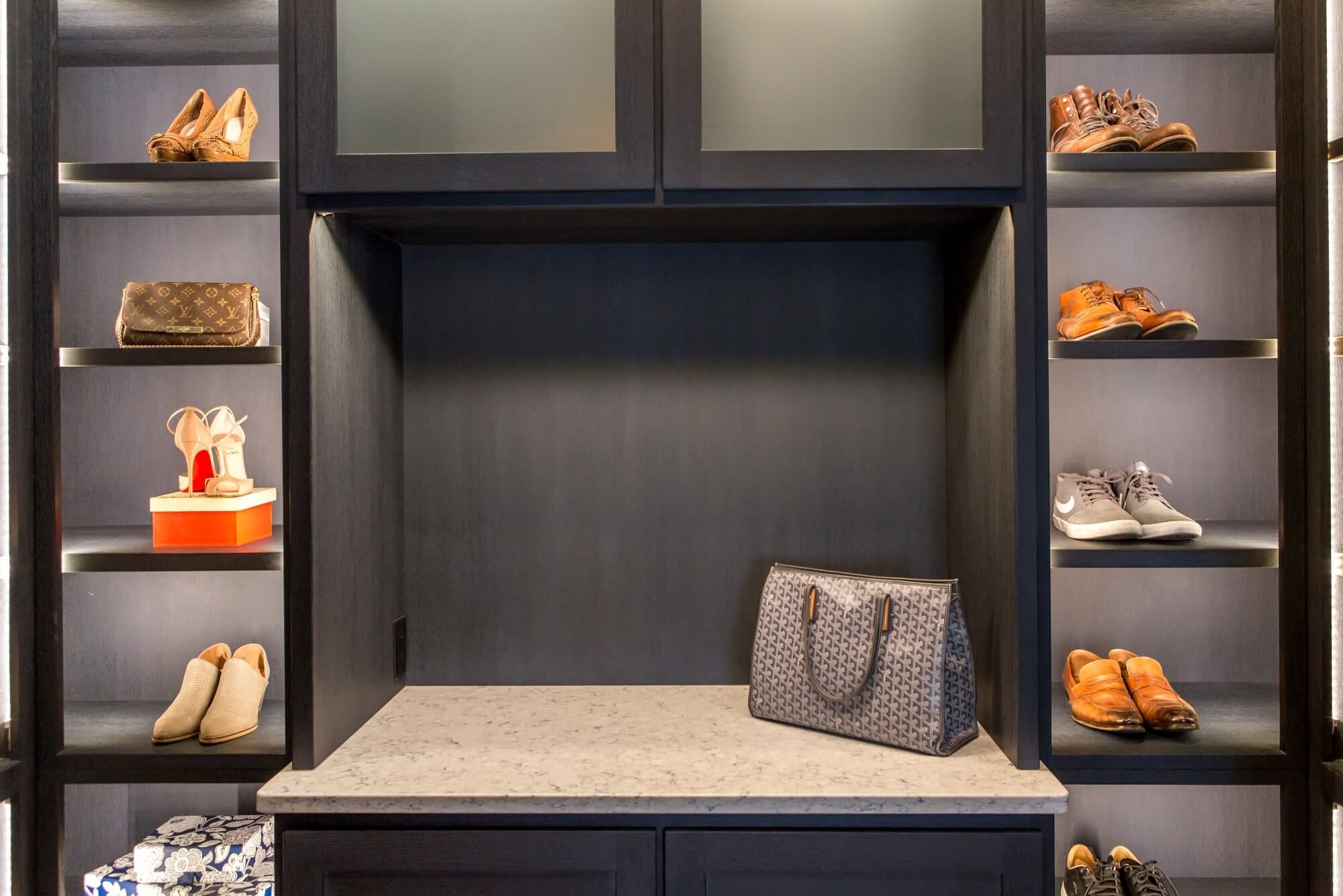 Lighted shoe shelving and accessory counter in a luxury closet.
