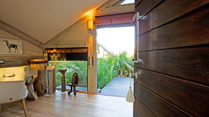 The room of a luxury safari lodge with wooden wall panels.