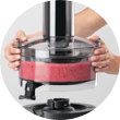 Both hands lifting juicer basin filled with pink fruit pulp