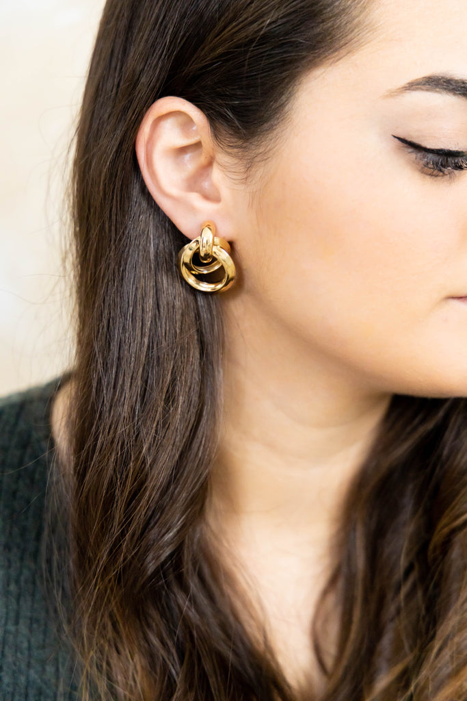 Gold drop earrings on model