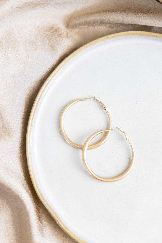 Gold hoop earrings on white background