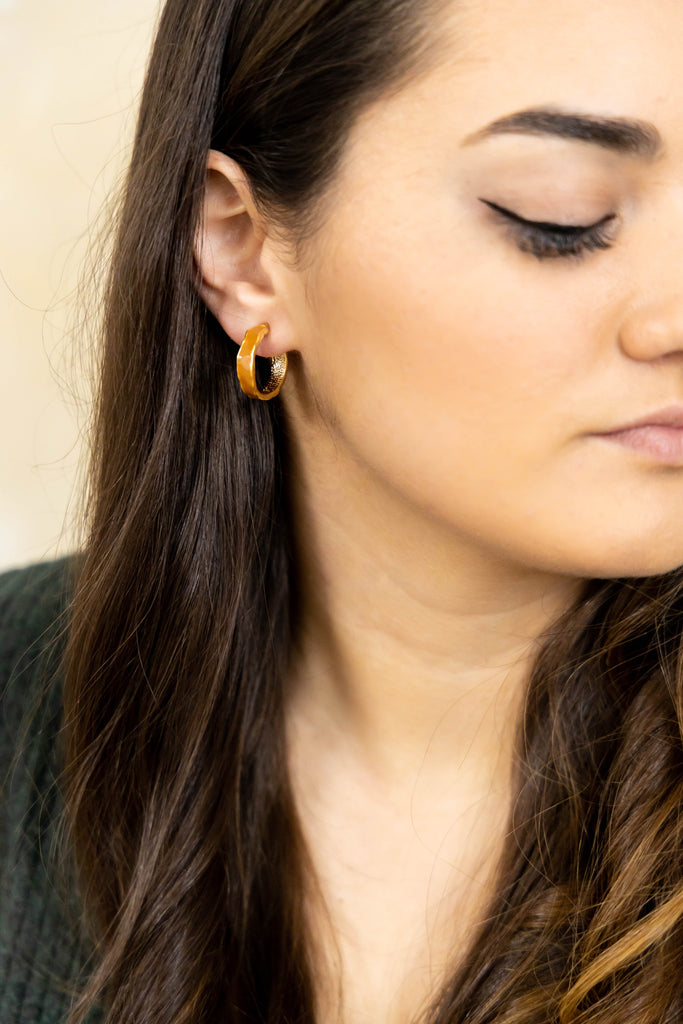 Gold and orange hoop earrings on model