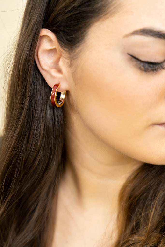 Gold and red hoop earrings on model