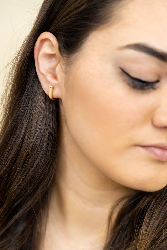 Gold stud earrings on model