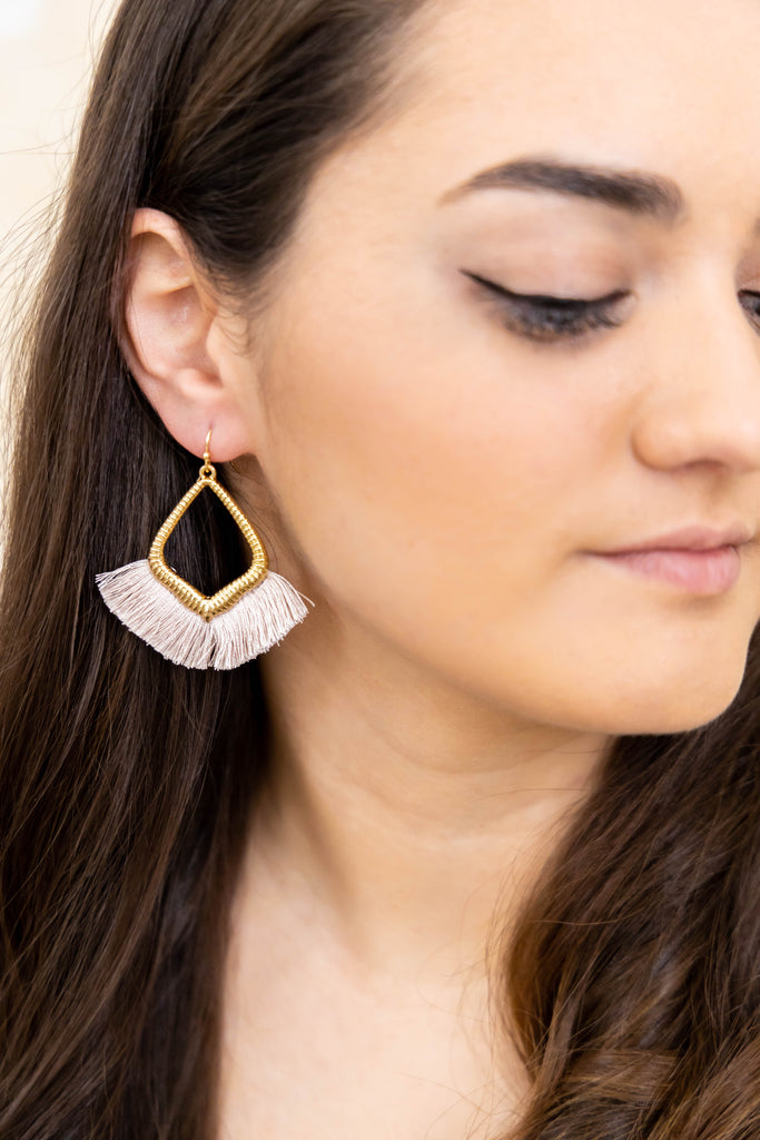 Gold earrings with blush threads on model