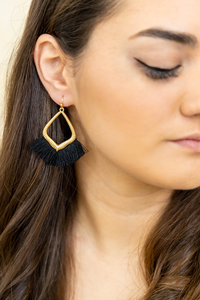 Gold earrings with black fringe threads on model