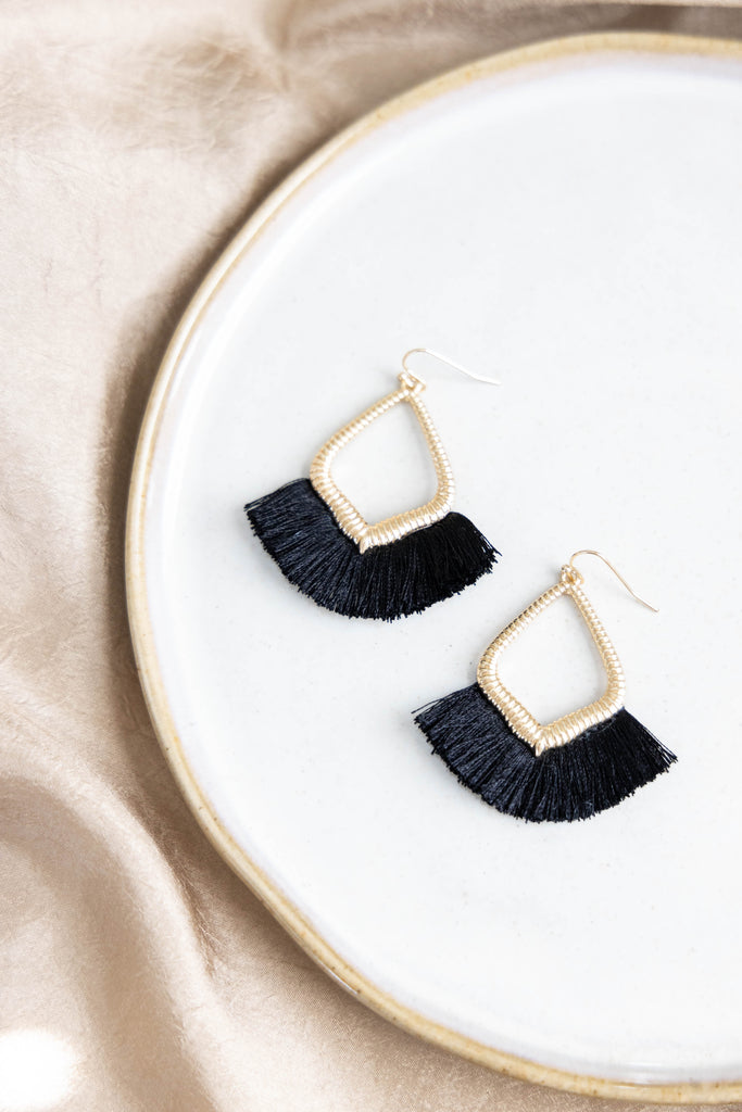 Gold earrings with black fringe threads on white background