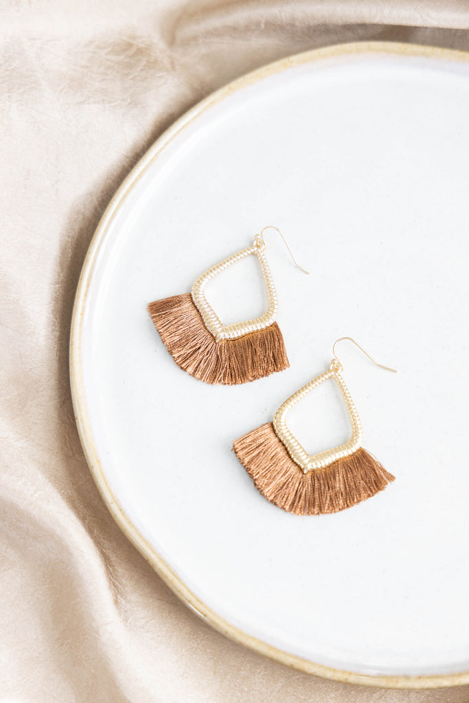 Gold earrings with taupe threads on white background