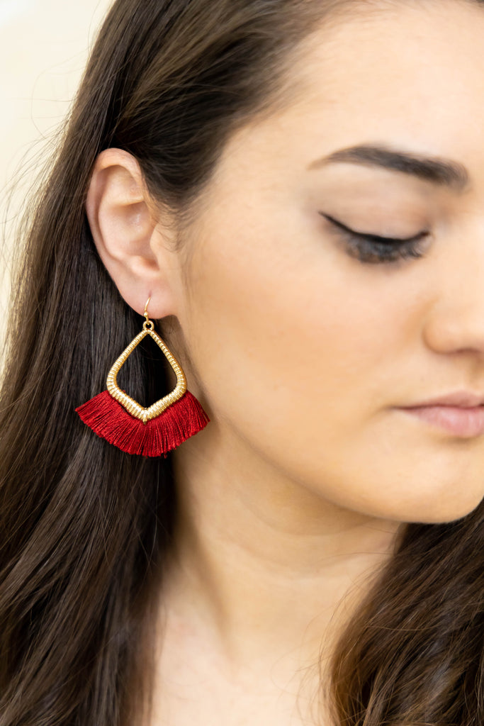 Gold earrings with red threads on model