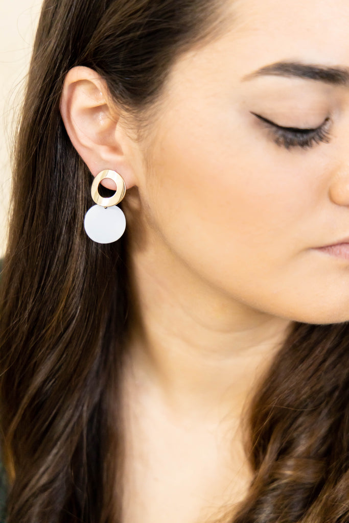 Gold and white earrings on model