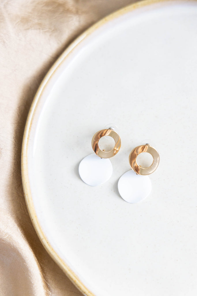 Gold and white earrings on white background