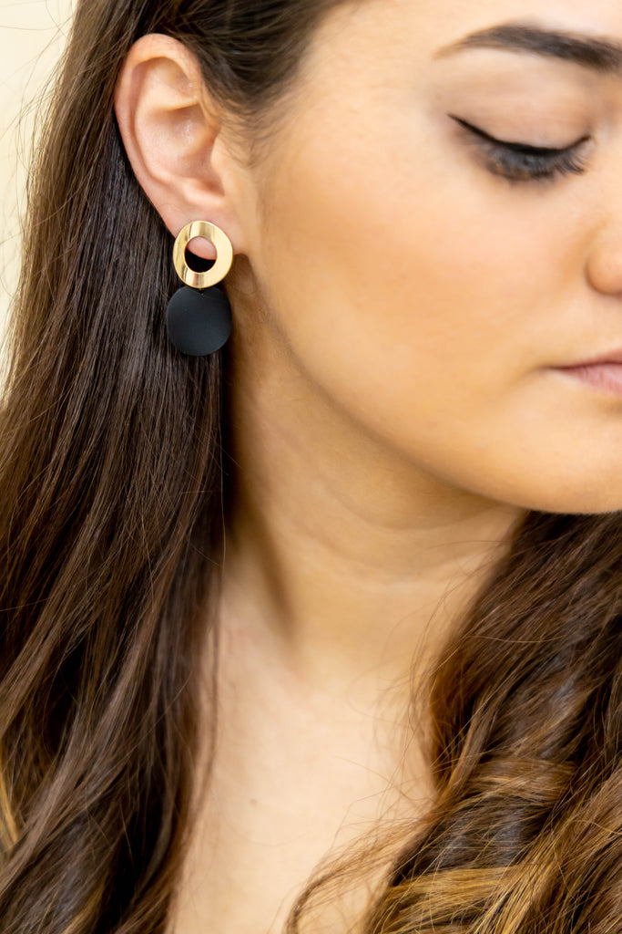 Gold and black earrings on model
