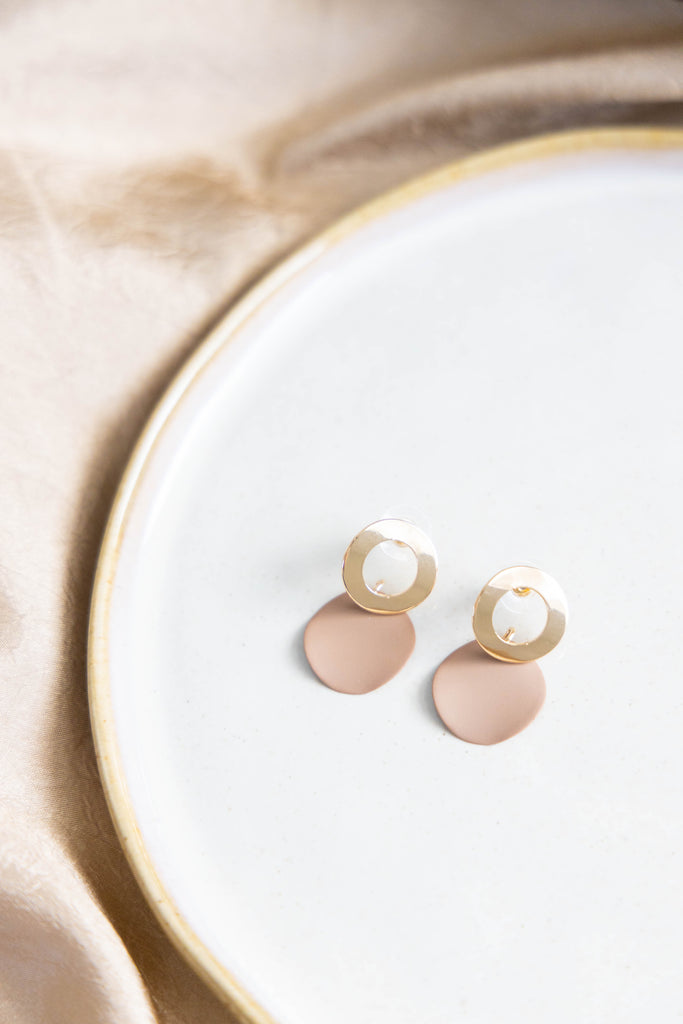 Gold and taupe earrings on white background