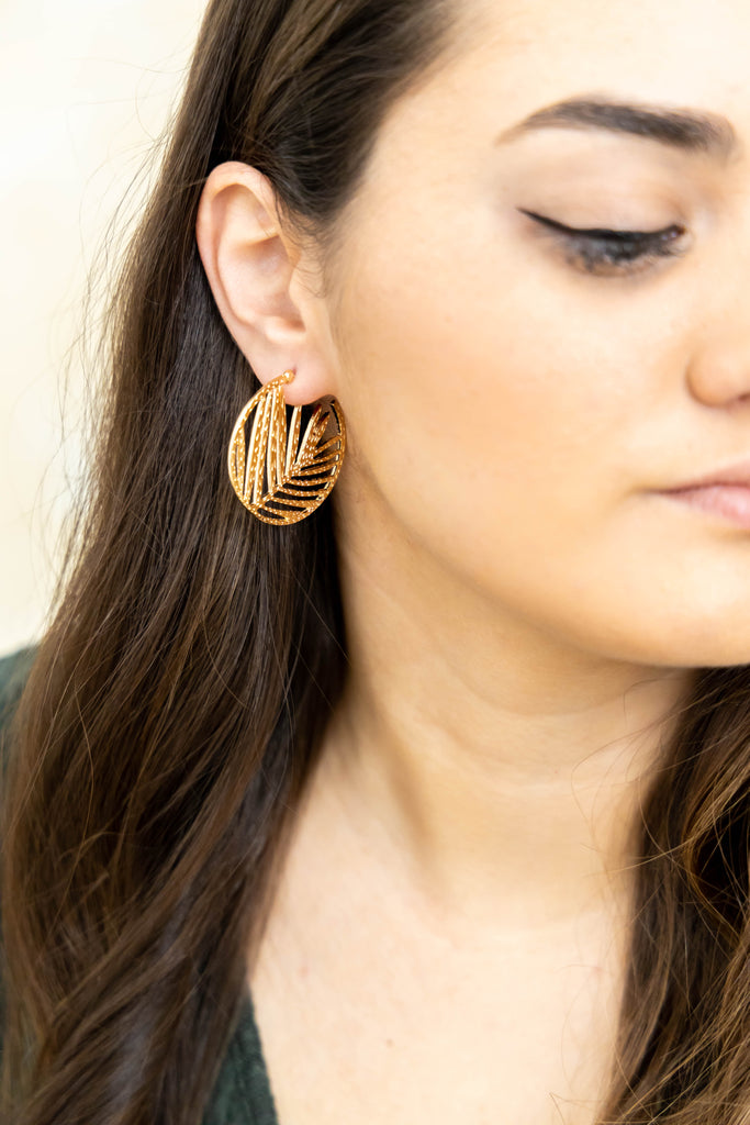 Gold hoop earrings with leaf design on model