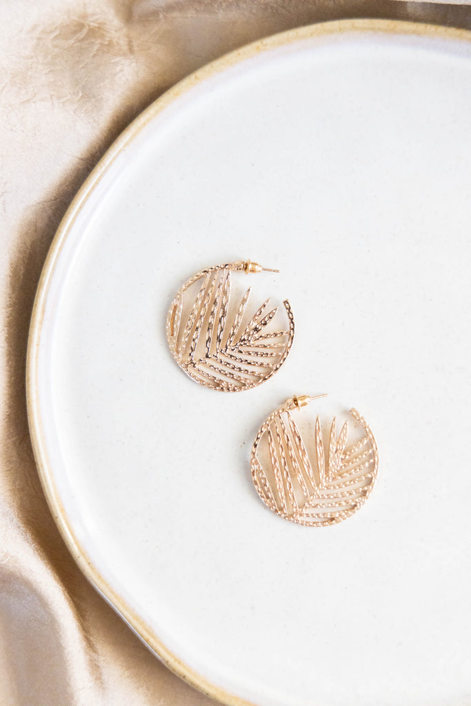 Gold hoop earrings with leaf design on white background