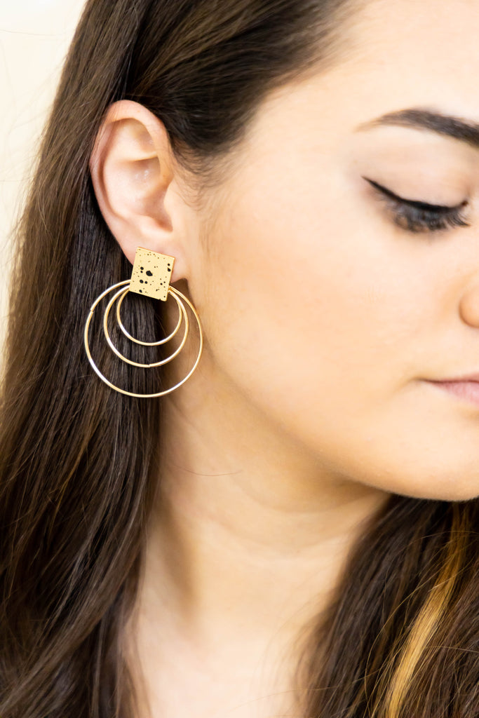 Gold, modern earrings on model