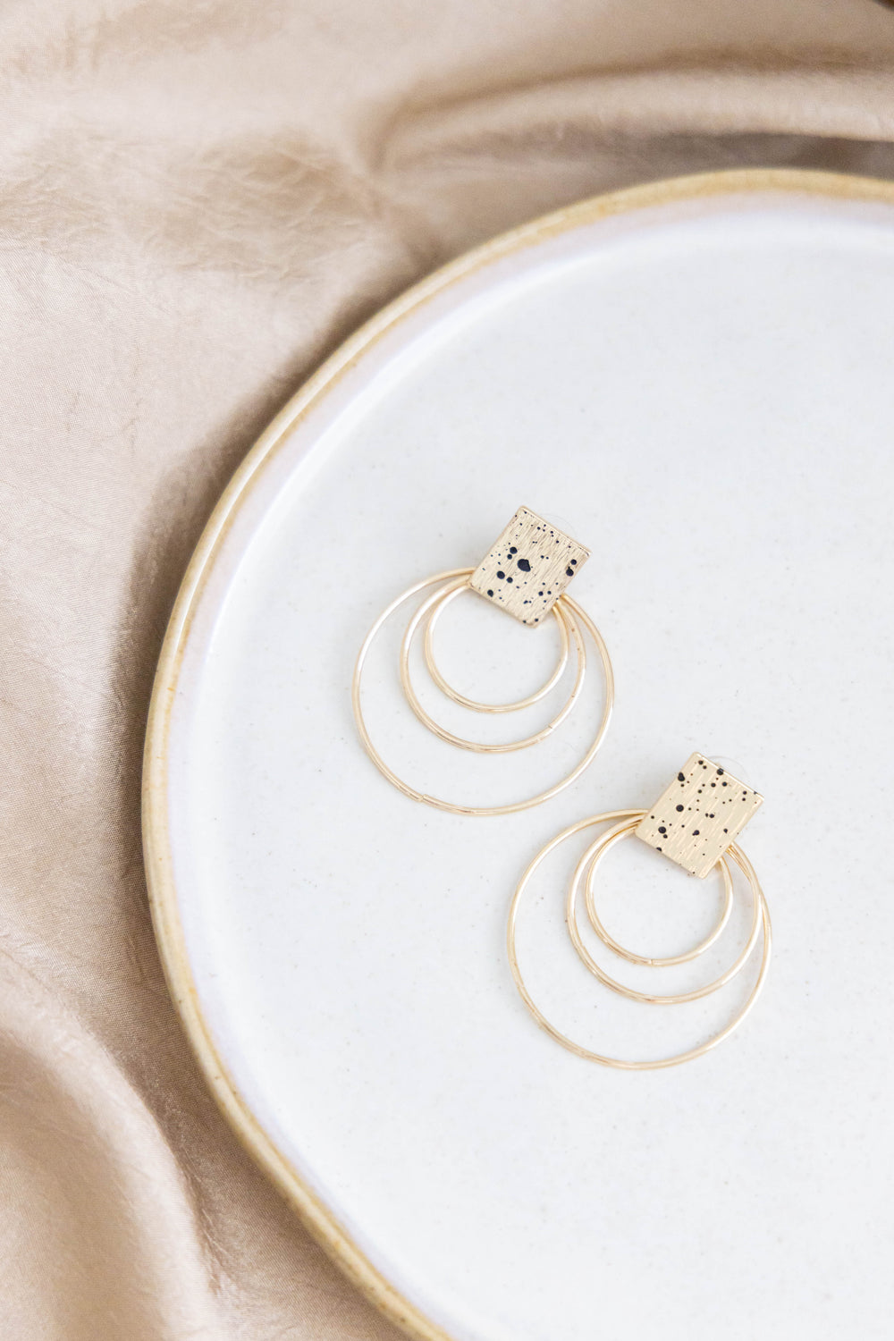 Gold, modern earrings with black spots