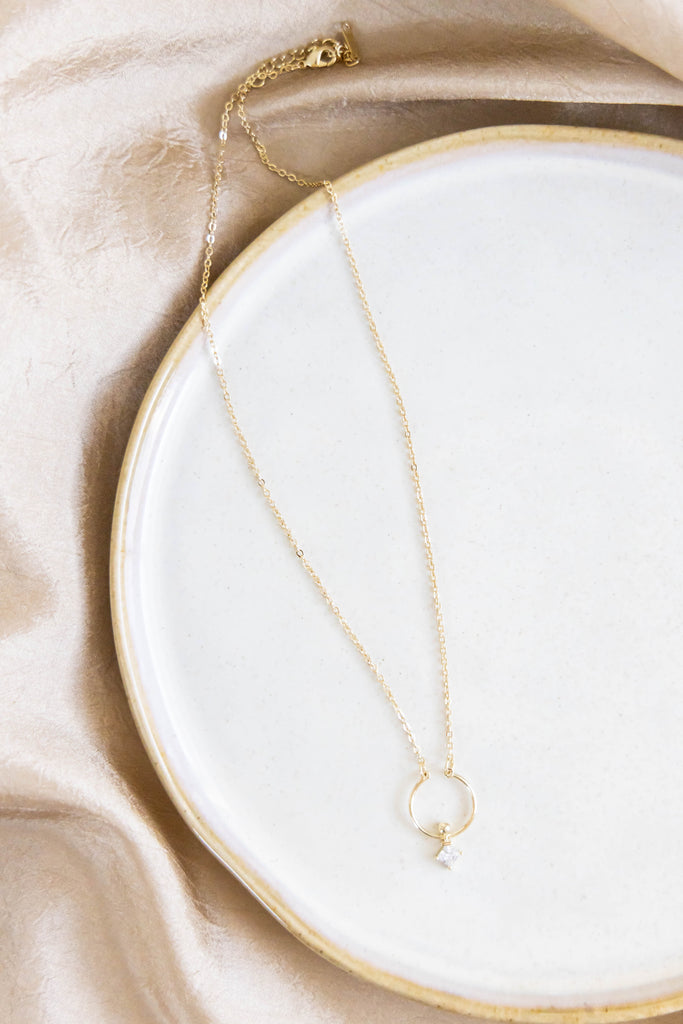 gold necklace with diamond pendant on plate
