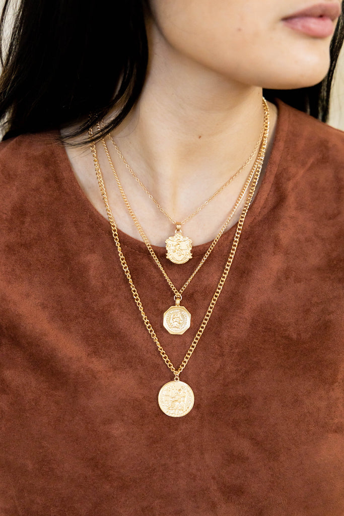 Gold layered coin necklace on model