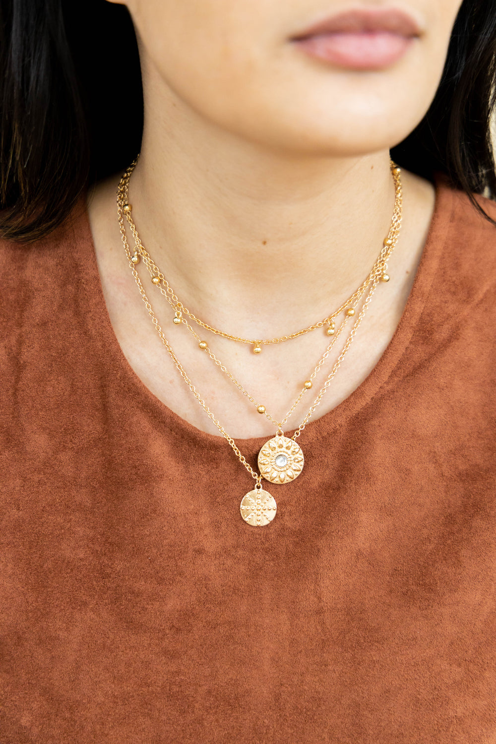 Gold layered necklace with pendants on model
