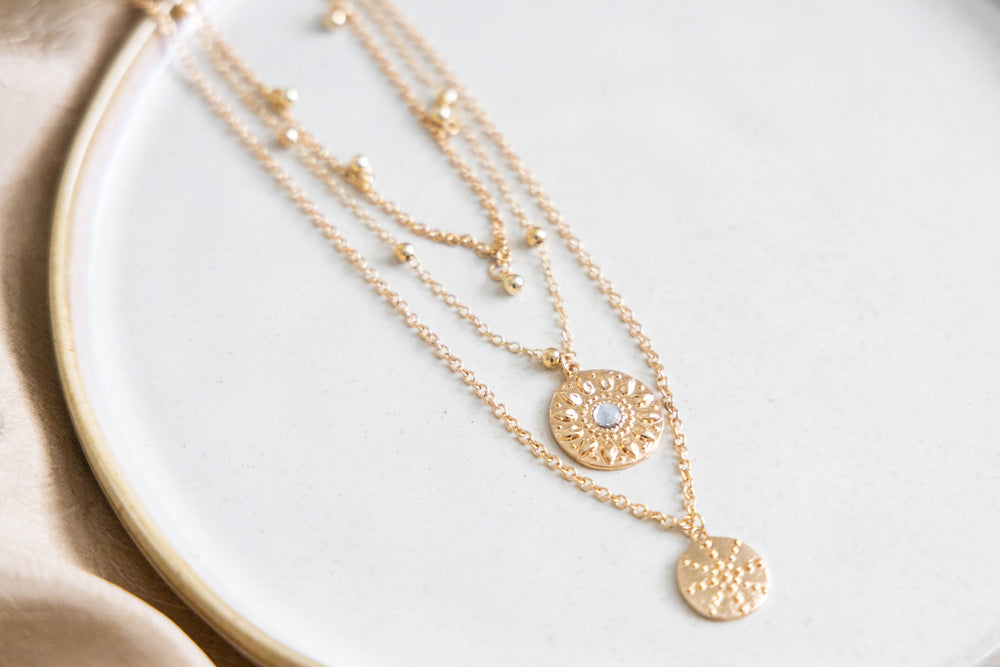 Gold layered necklace with pendants on white background