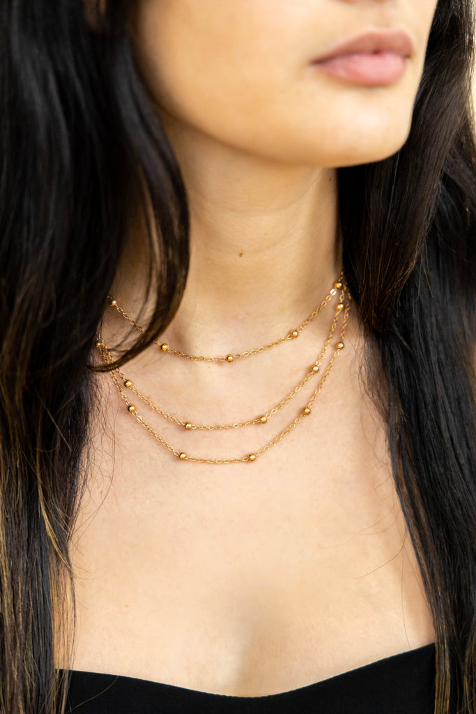 Gold layered necklace with beads on model