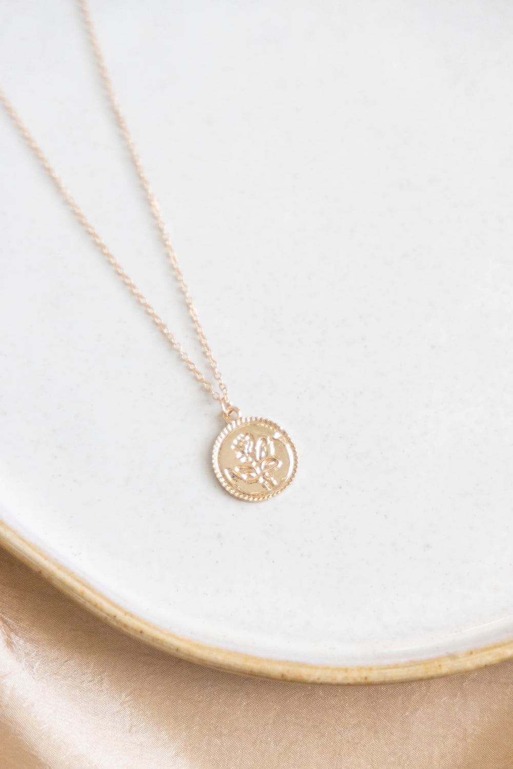 Gold necklace with rose pendant on white background