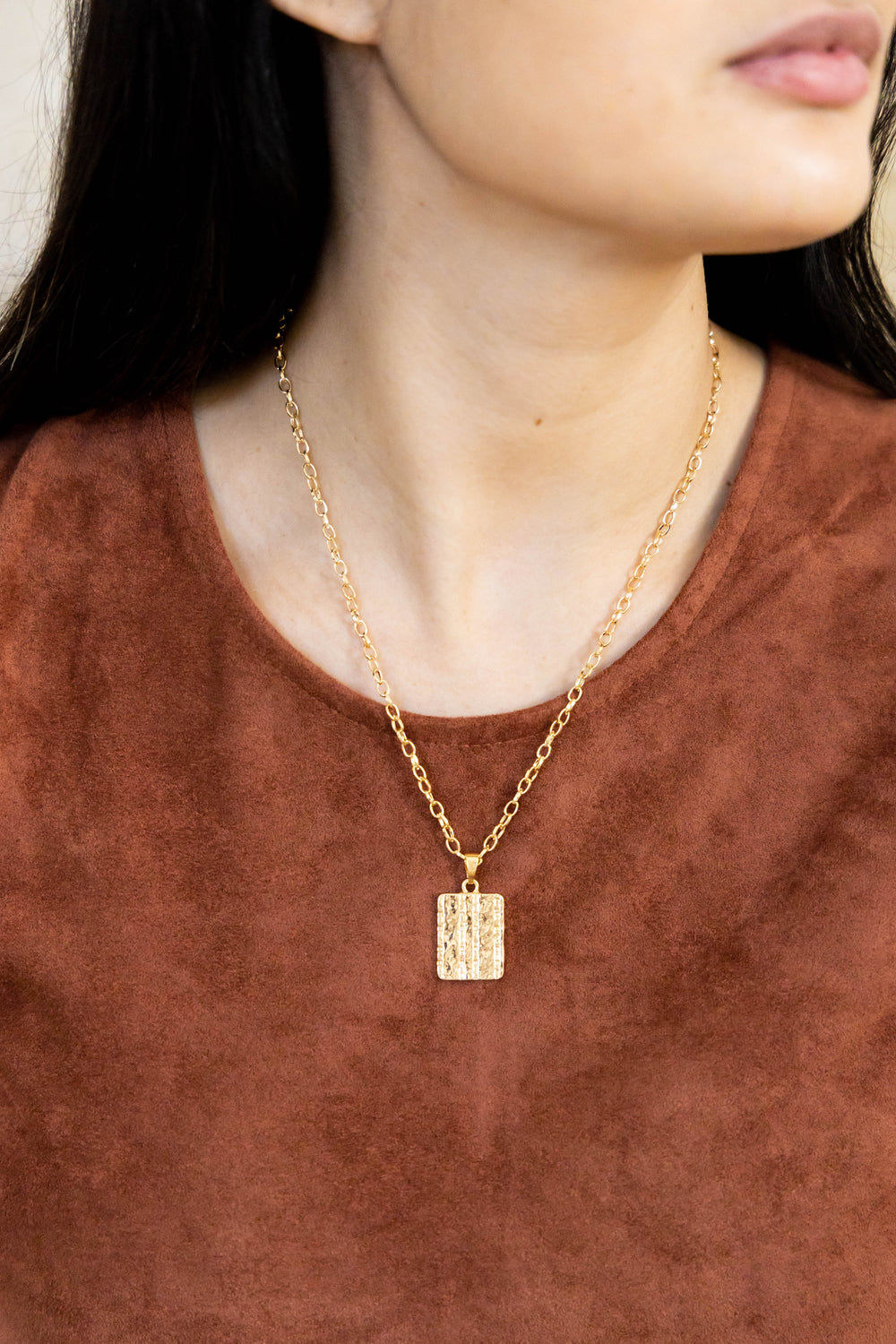 Gold necklace with rectangle pendant on model