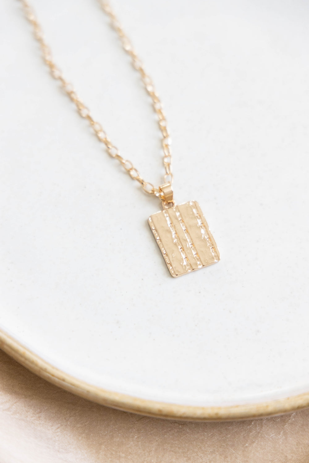 Gold necklace with rectangle pendant on white background