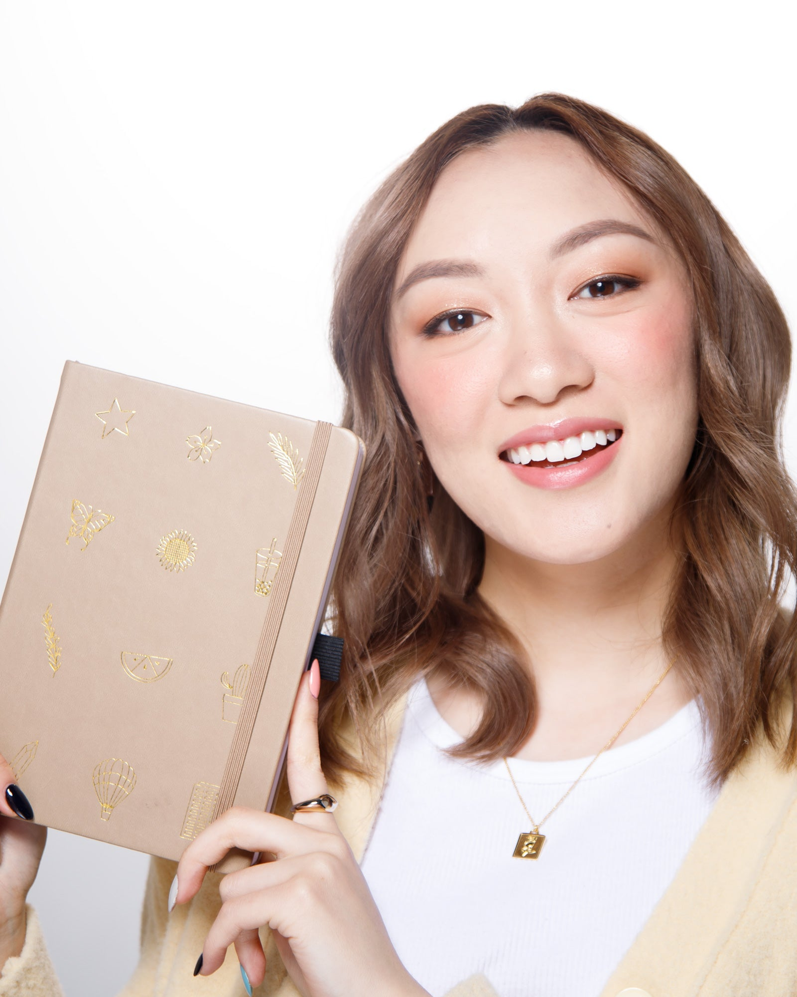 Amanda Rach Lee sitting smiling holding up a planner