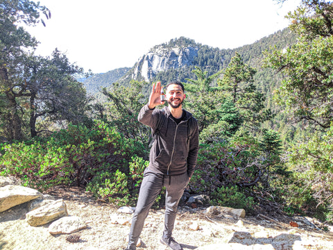 young man hiking in mountains holding cbd oil for pain relief - zehne