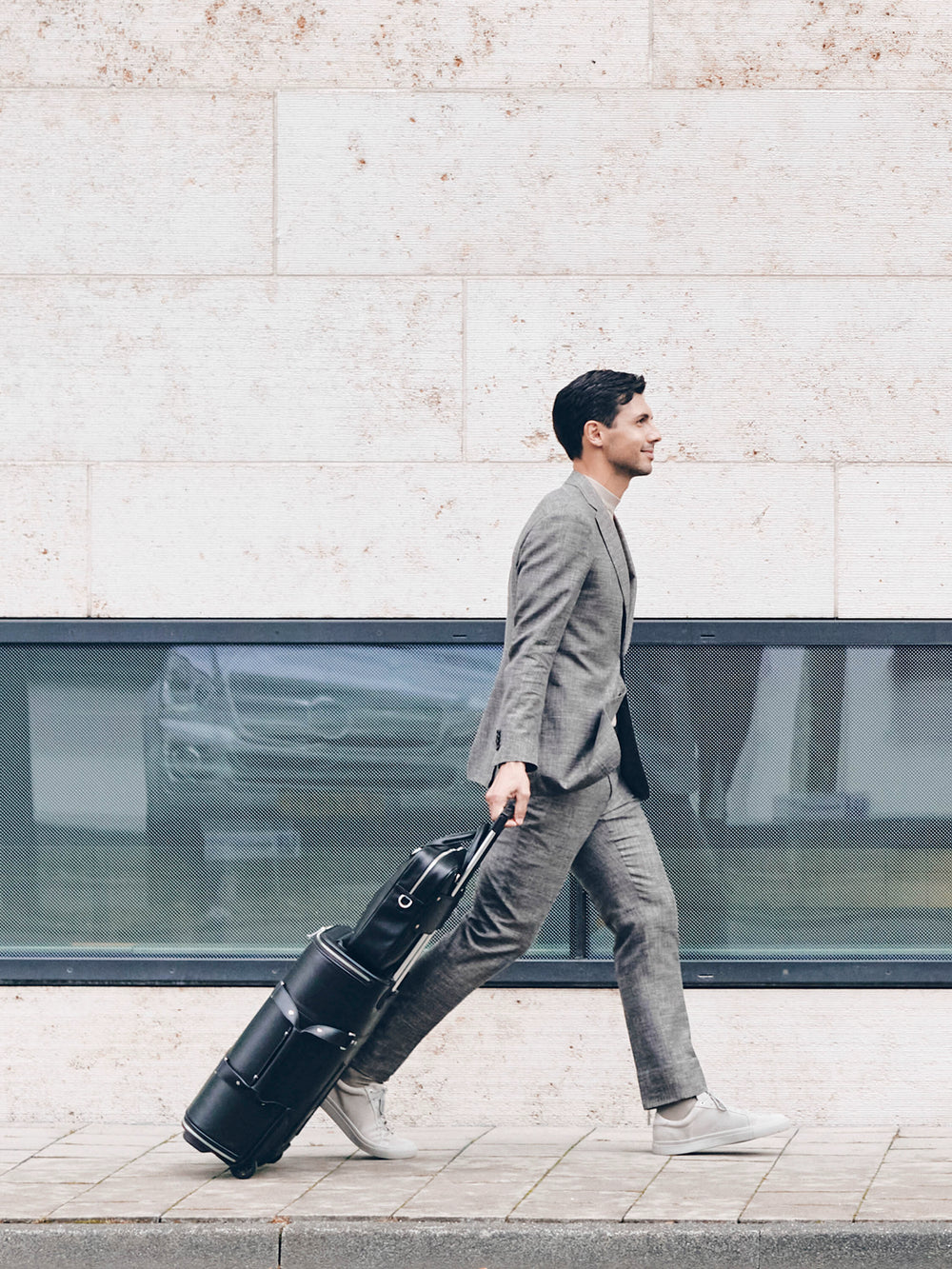 male model walking with f38 black carry-on luggage in italian leather black leather schwarzes leder