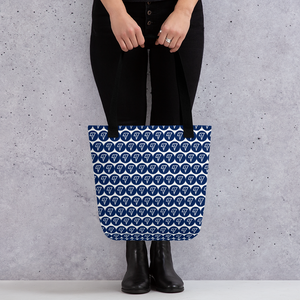 Adult woman holding a tote bag with the VuWing blue dot logo in a repeated pattern all over it and black straps. VuWing airplane travel phone holder for handsfree movies & tv while you travel