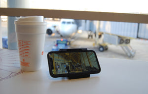 vuwing travel phone holder laying flat on a counter watching a movie with coffee