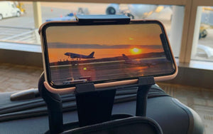 watching a movie of an airplane taking off on the vuwing travel phone holder hanging from a luggage handle in an airport terminal waiting area