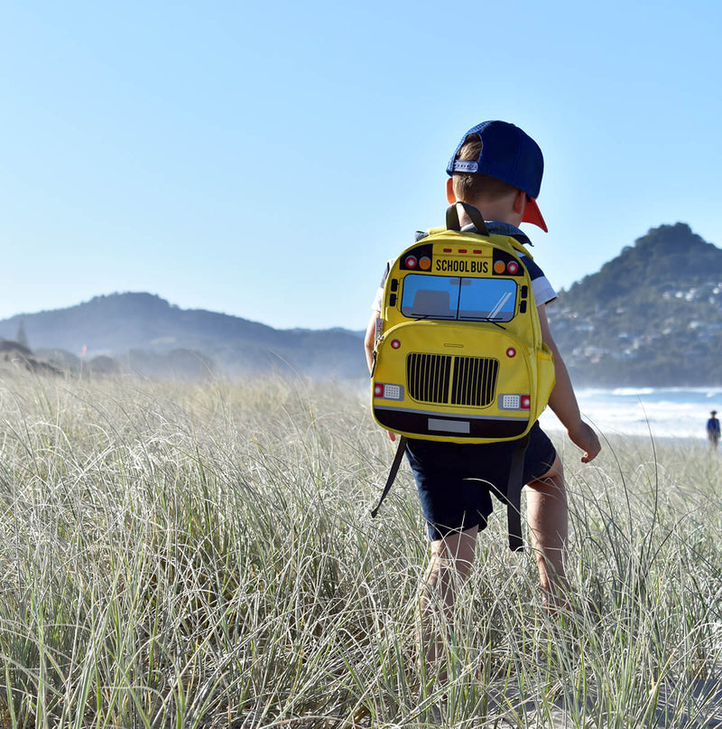 Boy on the beach wearing yellow school bus backpack by jude and moo.