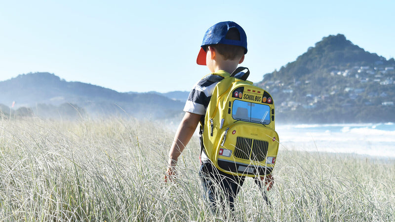 Boy walking along the beach wearing a jude&moo yellow bus backpack.