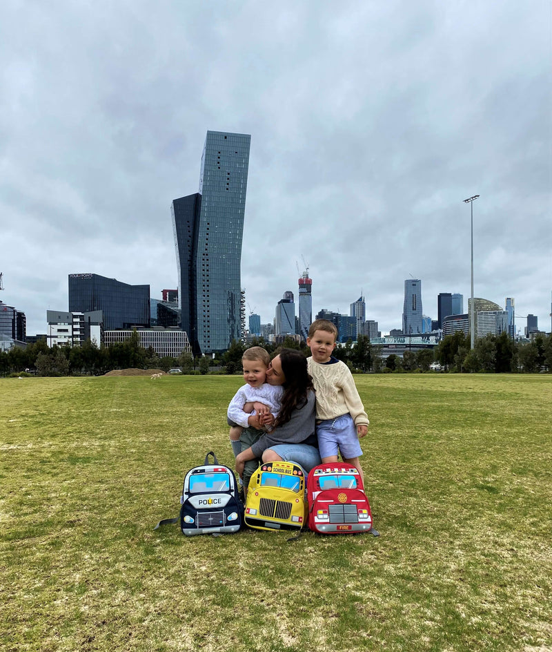 In Melbourne, jude&moo founder, Kate with her boys and the jude&moo collection of vehicle backpacks sitting on the grass in the Docklands.