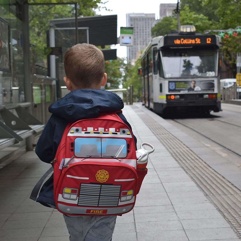 Boy wearing bright, red fire truck backpack while walking down a Melbourne CBD street.