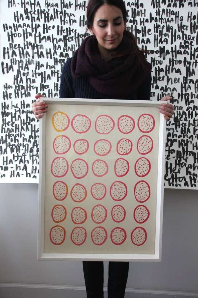 Kate Roebuck of Bowerbird Collective holding her favorite piece of art, a screenprint collaboration with Hable Construction, via Simply Framed