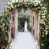 Floral decorated archway with ribbons dangling in the middle @elloirevents