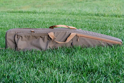 Rifle bag in grass with rifle inside. Armageddon Gear 52 Inch Precision Rifle Case - Sharps Mountain Outdoor Gear - Pigg River Precision
