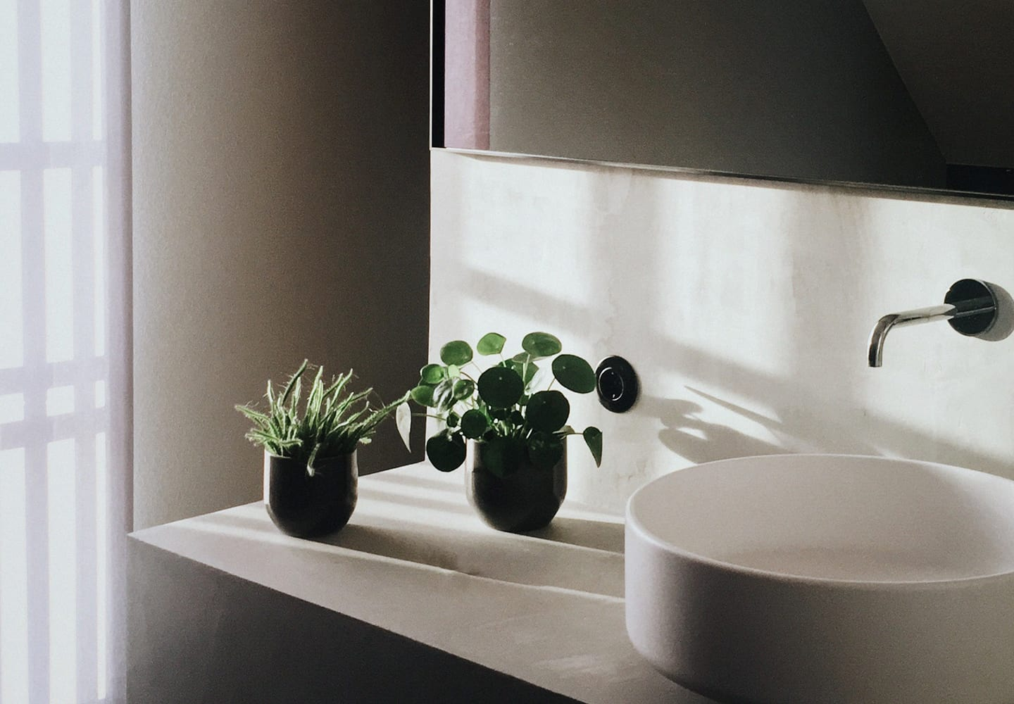 Soft lit bathroom counter and sink featuring small plants