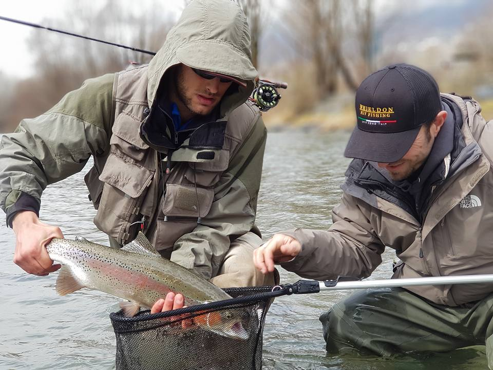 Two anglers holding a beautiful rainbow trout