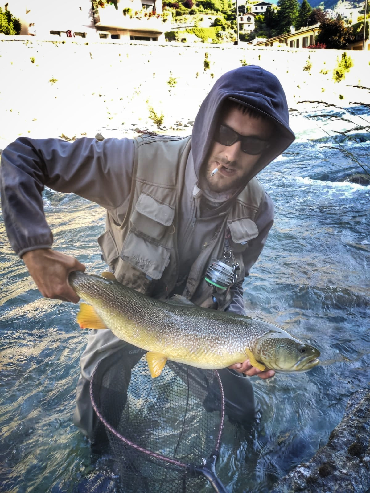 man caching marble trout fly fishing in italy
