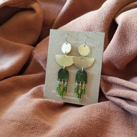 Earrings made with upcycled leather, seed beads, brass geometric shapes and hypoallergenic titanium ear wires. Forest green colored leather in arc shape with beaded fringe. Green and gold colored seed beads.