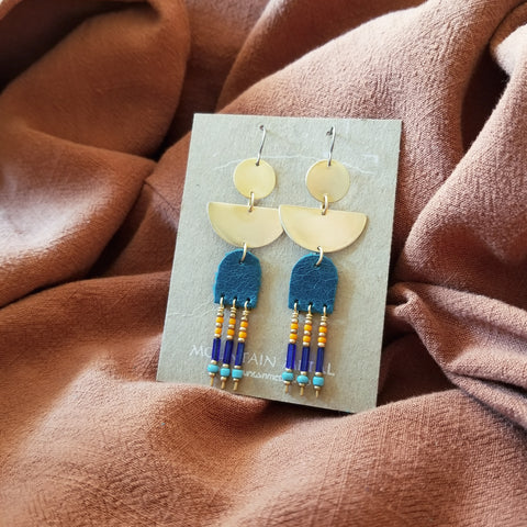 Earrings made with upcycled leather, seed beads, brass geometric shapes and hypoallergenic titanium ear wires. Blue colored leather in arc shape with beaded fringe. Turquoise, blue, orange, and gold colored seed beads.