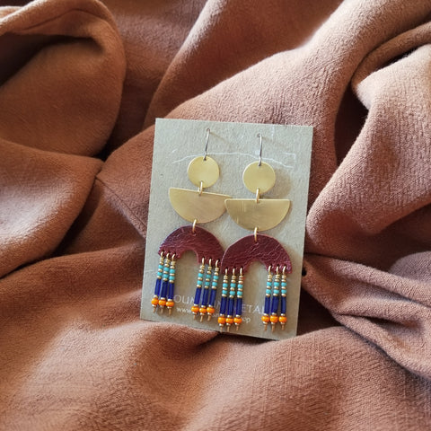 Earrings made with upcycled leather, seed beads, brass and hypoallergenic titanium ear wires. Merlot colored leather in rainbow shape with beaded fringe. Turquoise, blue, orange, and gold colored seed beads.